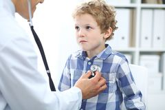 Doctor and child patient. Physician examines little boy by stethoscope. Medicine and children`s therapy concept.  Royalty Free Stock Images