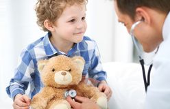 Doctor and child patient. Physician examines little boy by stethoscope. Medicine and children`s therapy concept stock photography
