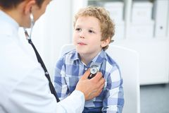 Doctor and child patient. Physician examines little boy by stethoscope. Medicine and children`s therapy concept.  Stock Image