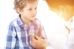 Doctor and child patient. Physician examines little boy by stethoscope. Medicine and children`s therapy concept.  stock photo
