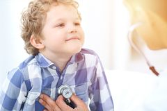 Doctor and child patient. Physician examines little boy by stethoscope. Medicine and children`s therapy concept stock images