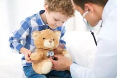 Doctor and child patient. Physician examines little boy by stethoscope. Medicine and children`s therapy concept.  royalty free stock photography