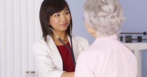 Doctor chino que escucha el corazón del paciente mayor Foto de archivo libre de regalías