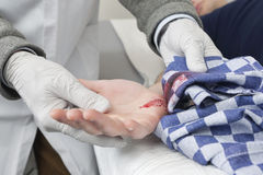 Doctor Cleaning a Bleeding cut With Cloth Royalty Free Stock Image