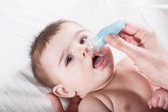 Doctor cleans the nose of little baby. Royalty Free Stock Photo