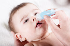 Doctor cleans the nose of little baby. Royalty Free Stock Photography