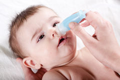 Doctor cleans the nose of little baby. Royalty Free Stock Images