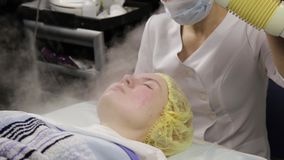 Doctor cleanses the woman's skin with a steam. Young woman with problem skin at the beautician. Cosmetology concept stock video footage