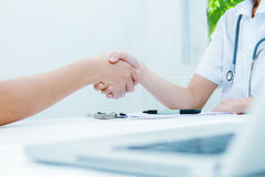 Doctor at the clinic giving an handshake to his patient, healthc Royalty Free Stock Image