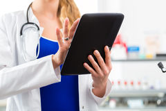 Doctor in clinic reading digital file on tablet computer Stock Image