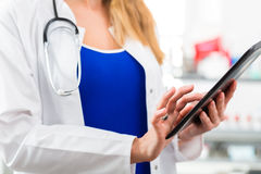 Doctor in clinic reading digital file on tablet computer Stock Photography