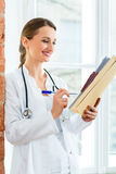 Doctor in clinic writing in a file Stock Images