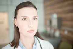 Doctor in clinics. Young female in medical uniform looking at you during work in her clinics Stock Photos
