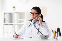 Doctor with clipboard calling on phone at hospital. Medicine, people and healthcare concept - happy female doctor with papers and clipboard calling on phone at Royalty Free Stock Photos