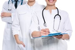 Doctor with clipboard and colleagues on white background. Unity concept stock photography