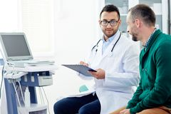 Medical prescriptions. Doctor with clipboard consulting one of patients and making prescriptions Stock Images
