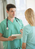 Doctor With Clipboard Explaining Report To Patient In Clinic Royalty Free Stock Image
