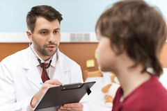 Doctor with clipboard looking at little boy patient in hospital Stock Photo