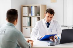 Doctor with clipboard and male patient at hospital stock photos