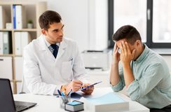 Doctor with clipboard and male patient at hospital. Medicine, healthcare and people concept - doctor with clipboard talking to devastated male patient at medical royalty free stock images