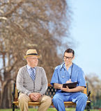Doctor with clipboard and senior sitting in park Royalty Free Stock Photo