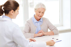 Doctor with clipboard and senior woman at hospital Royalty Free Stock Photo
