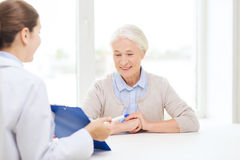 Doctor with clipboard and senior woman at hospital Royalty Free Stock Images