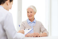 Doctor with clipboard and senior woman at hospital Stock Images
