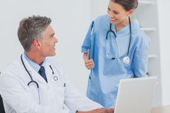 Doctor with a clipboard talking to a colleague Stock Photography