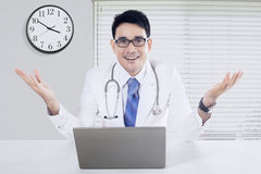 Doctor with clock and laptop in office Royalty Free Stock Photography