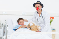 Doctor in clown costume with boy in hospital Stock Photo
