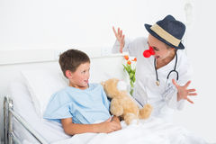 Doctor in clown costume entertaining ill boy in hospital Royalty Free Stock Images