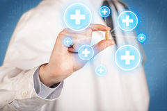 doctor in coat in front of a blue wall holding a pill between his fingers with lines Royalty Free Stock Image