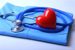 Doctor coat with medical stethoscope and red heart on the desk stock images