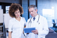 Doctor and colleague looking in digital tablet Royalty Free Stock Image