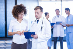 Doctor and colleague looking at medical report. And having a discussion Royalty Free Stock Photography