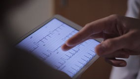 Doctor with colleagues examines the tablet cardiogram. stock video