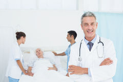 Doctor with colleagues and patient behind Royalty Free Stock Photo