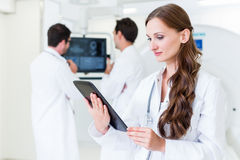 Doctor with colleagues standing in hospital at CT machine with s. Can results Royalty Free Stock Images