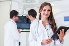 Doctor with colleagues standing in hospital at CT machine with s Stock Photography