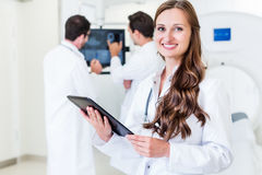 Doctor with colleagues standing in hospital at CT machine with s. Can results Royalty Free Stock Image