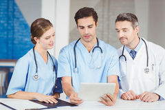 Doctor and colleagues using digital tablet while standing at desk Royalty Free Stock Photography