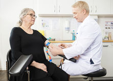 Doctor Collecting Senior Patient's Blood For Test In Clinic. Mature male doctor collecting senior patient's blood for test in clinic royalty free stock photography
