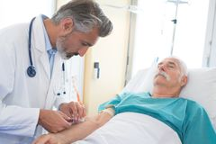 Doctor collecting senior patients blood for test in hospital. Blood stock photos
