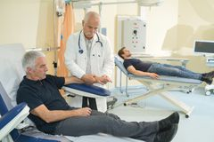 Doctor collecting senior patients blood for test in hospital. Mature royalty free stock images