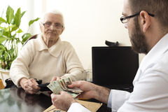 The doctor collects a fee from an old lady in a private doctor`s office. A doctor with a patient in the doctor`s office. The doctor collects a fee from an old Stock Photos
