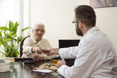 The doctor collects a fee from an old lady in a private doctor`s office. A doctor with a patient in the doctor`s office. Grandma pays the doctor for a visit to Stock Photo