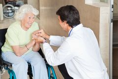 Doctor Comforting Happy Senior Woman. Young doctor comforting happy senior women in hospital Stock Photo