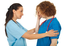 Doctor comforting her colleague Stock Image