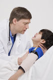 Doctor comforting little boy patient Stock Photography